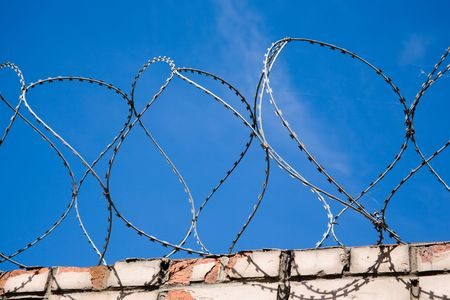barblock: loops of barbwire in front of blue sky