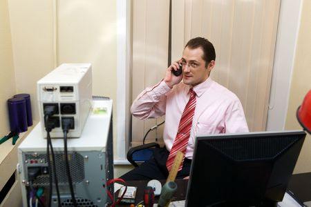 system administrator at the computer speaking on his mobile phone photo