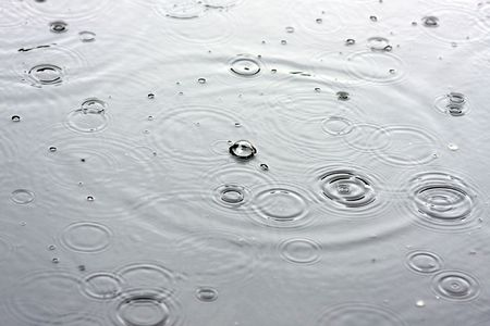 Drops of a rain in water close up