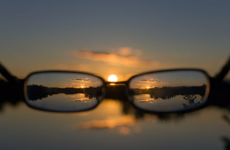 view on a sunset on lake through glasses photo