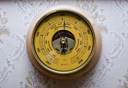 atmospheric pressure: Yellow barometre against wall-paper with patterns Stock Photo