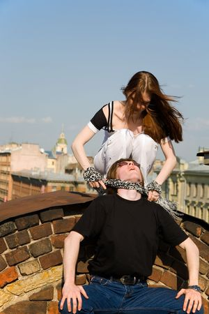smother: young woman strangling a young man on a petersburgs roof