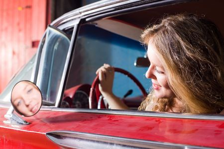 The beautiful girl looks in a car mirror photo