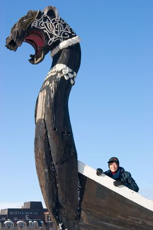 Smiling woman on the board of old Viking ship photo