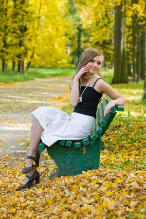 The beautiful girl on a bench in autumn park photo