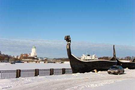 Vyborgs quay in winter: modern car near ancient vessel  photo