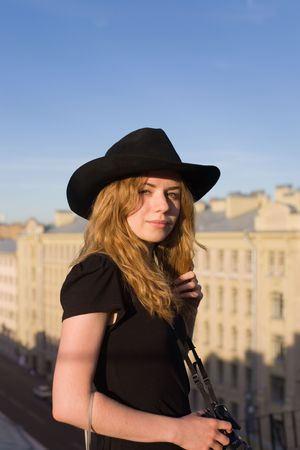 The young blonde in a hat standing on a roof photo