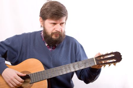 The man adjusting an acoustic guitar photo