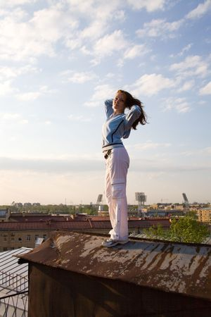 serenety: young girl standing on a twilight petersburgs roof Stock Photo