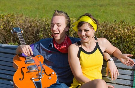 The young man and the girl with a guitar on a bench in park Stock Photo - 4283074