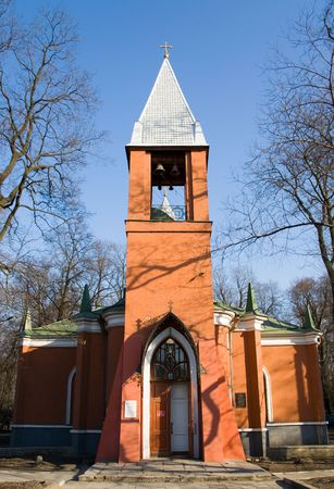 bared: Neo-Gothic bell tower and bared trees against a blue sky Stock Photo