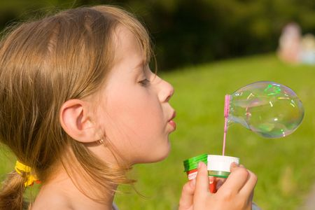 The girl and a soap bubble in sunny day photo