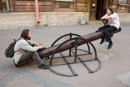 imbalance: Jong lachend paar zitten op Teeter-waggelen op straat in de zomer