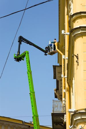 worker renovating the facade of a building at height photo