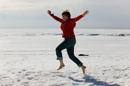 The cheerful girl runs barefoot on snow photo