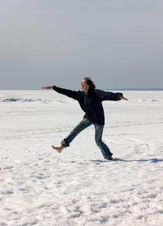 The cheerful girl runs barefoot on snow photo