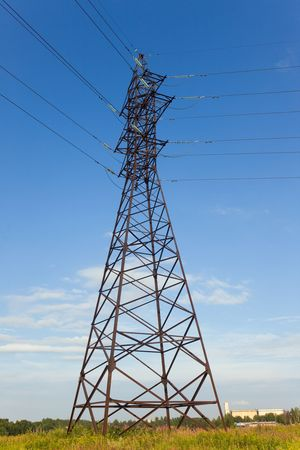 Transmission line tower on city suburb in sunny day photo