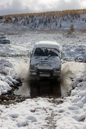 The car moves ford in mountain small river in the winter photo