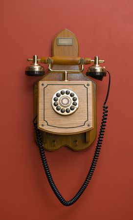 Wooden retro phone on a red wall Stock Photo - 5859325