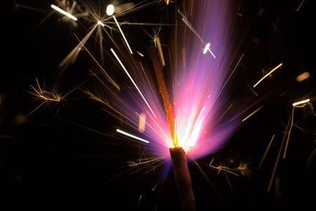 Burning violet fireworks on a black background photo