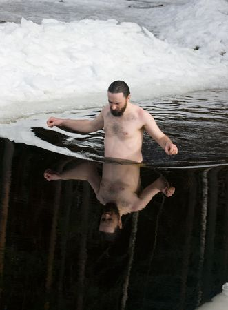The man comes into an ice-hole in winter lake photo