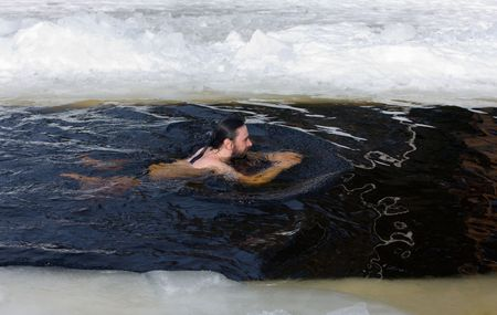 The man swimming in an ice-hole on lake photo