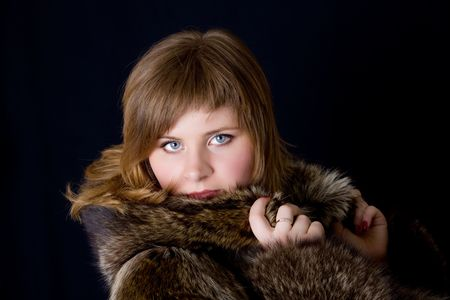 The girl in a fur coat on a black background Stock Photo - 6713657