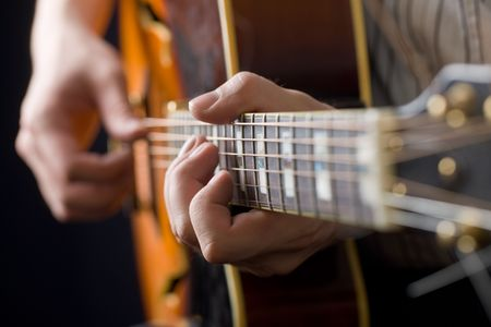 Hands of the playing guitarist close up
