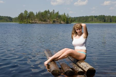 The girl has a rest on a raft in lake photo