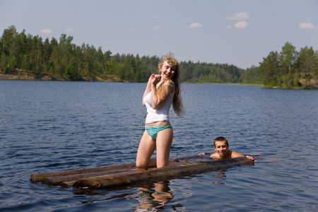 The man drives the girl on a raft in lake photo