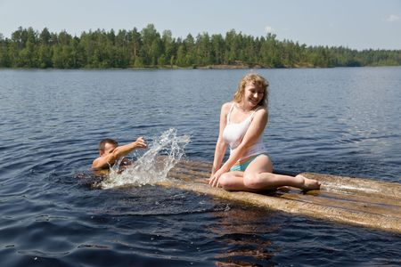 The man and the woman have a rest on lake in the summer photo
