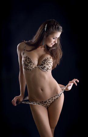 The sexual brunette in bikini on a black background