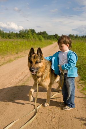 The little boy with a dog on rural road photo