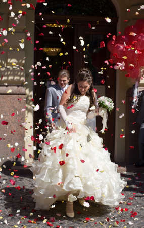 Newly married shower with petals of roses and coins Stock Photo - 8531577