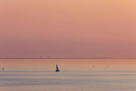 Pink twilight over gulf of Finland with a lonely sailing vessel photo