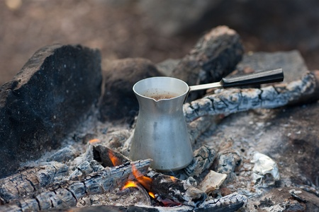 Coffee cooking on fire coals close up photo