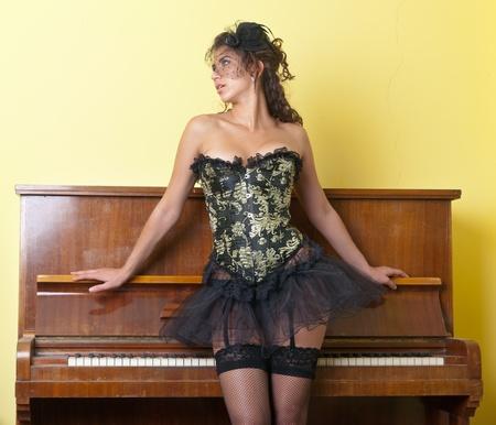 The girl in a corset on the piano photo