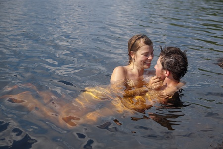 Loving couple in the summer water lake