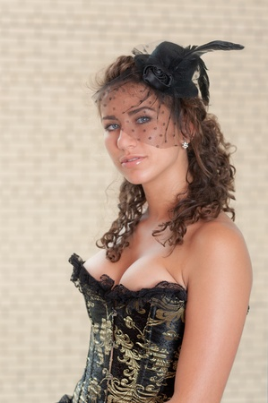 The girl in a corset and a hat against a wall photo