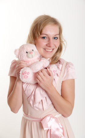 The girl in a pink dress with a soft toy photo
