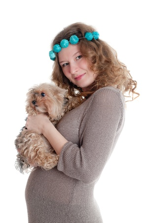 The pregnant woman with a puppy in hands photo
