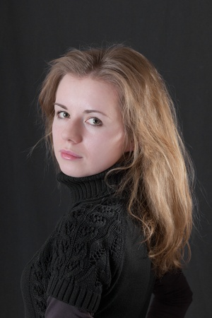 Portrait of the girl with a fair hair on a black background photo
