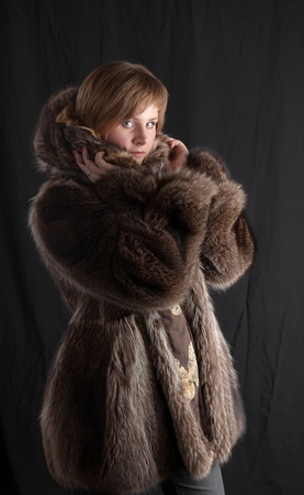 girl in a fur coat on black background photo