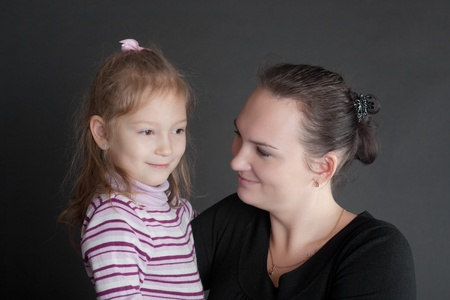 portrait of mother with the daughter on a black background photo
