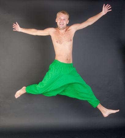 the jumping man in green trousers on a black background photo