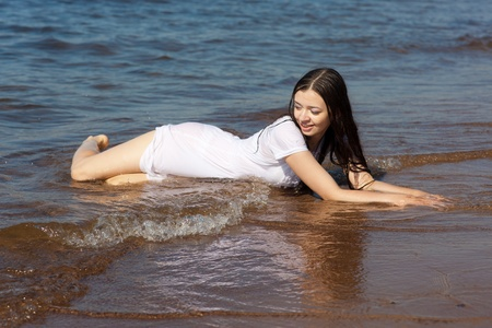 the girl in a white dress lies in a surf strip