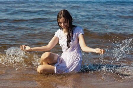 the cheerful girl in a white dress on the seashore