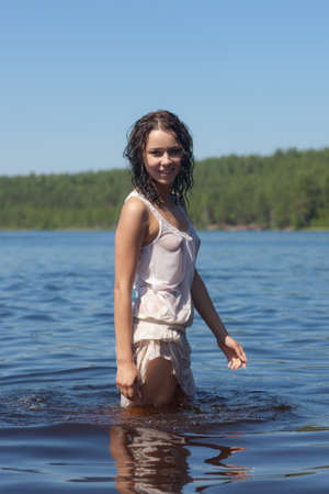 girl in a white wet dress in lake water