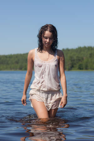 girl in a white wet dress in lake water photo