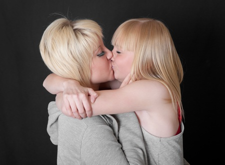 kiss of two blondes on a black background photo